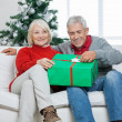 Couple With Christmas Gift Sitting On Sofa — Stock Photo
