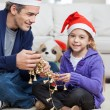 Girl With Father Holding Christmas Ornaments — Stock Photo #34277117