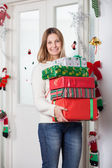 Woman With Gifts Standing By Door During Christmas — Fotografia Stock