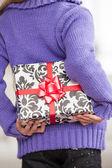 Girl Hiding Christmas Gift Behind Back — Stock fotografie