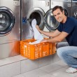 Stock Photo: Young Man Putting Clothes In Washing Machine