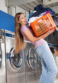 Woman Carrying Heavy Basket Of Clothes — Stock Photo