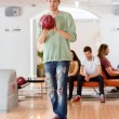Stock Photo: Young MHolding Bowling Ball in Club