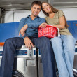 Stock Photo: Couple With Laundry Basket Sitting On Washing Machines