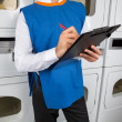 Male Helper Writing On Clipboard In Laundromat — Stock Photo