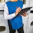 Male Helper Writing On Clipboard In Laundromat — Stock Photo #34381445