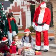 SantClaus Looking At Children Opening Gifts — Stock Photo #34381459