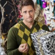 Man With Christmas Gift Biting Lips In Store — Stock Photo #34381945