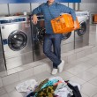 Happy Man Holding Empty Basket With Dirty Clothes On Floor — Stock Photo