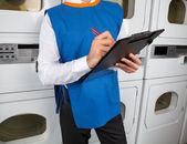 Male Helper Writing On Clipboard In Laundromat — Stock Photo