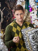 Man With Christmas Gift Biting Lips In Store — Stock Photo