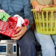 Couple With Laundry Baskets Sitting On Washing Machines — Stock Photo