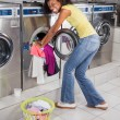 Stock Photo: Woman Pushing Clothes In Washing Machine