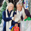 Senior Couple Using Digital Tablet At Christmas Store — Stock Photo