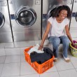 Stock Photo: Woman With Baskets Of Dirty Clothes Sitting At Laundromat