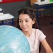 Schoolgirl Smiling While Searching Places On Globe — Stock Photo