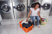 Woman With Baskets Of Dirty Clothes Sitting At Laundromat — Stock Photo