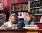 Schoolboys Looking Away While Sitting In Library — Stock Photo