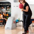 Young Woman Playing in Bowling Alley At Club — Stock Photo #34410589