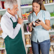 Senior Male Owner Assisting Female Customer In Choosing Product — Stock Photo