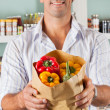 Stock Photo: Male Customer Showing Bellpeppers In Paper Bag