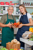 Saleswoman Holding Vegetable Basket Standing With Male Colleague — Stockfoto