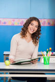 Teacher With Book Sitting At Desk In Classroom — Stock Photo