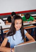 Glad teenage skolflicka sitter med laptop på skrivbordet — Stockfoto