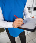 Male Helper Checking List In Laundry — Stock Photo