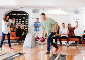 Man Bowling With Friends Cheering in Club — Stock Photo