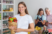 Woman Holding Grocery Bag While People Shopping In Background — Stock Photo