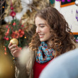 Woman Looking At Golden Bauble In Store — Stock Photo