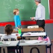 Schoolboy And Teacher Standing By Board In Classroom — ストック写真