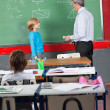 Schoolboy And Teacher Standing By Board In Classroom — 图库照片