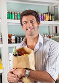 Człowiek z warzywo worek w sklepie spożywczym — Zdjęcie stockowe