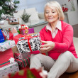 Senior Woman Looking At Christmas Gift — Stock Photo #34857295