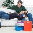 Couple With Christmas Presents Relaxing On Sofa — Stock Photo #34857923