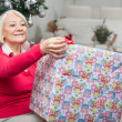 Senior Woman Opening Christmas Present — Stock Photo