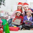 Stock Photo: Family Sitting By Christmas Gifts