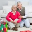 Happy Senior Couple Sitting By Christmas Presents — Stock Photo