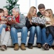 Family With Christmas Presents Sitting In House — Stock Photo
