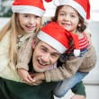 Playful Father Piggybacking Children During Christmas — Stock Photo