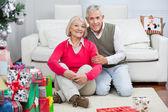 Gelukkige senior paar zitten door kerst presenteert — Stockfoto