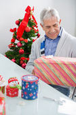 Man Looking At Wrapped Christmas Present — Stockfoto