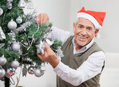 Happy Senior Man Decorating Christmas Tree — Stockfoto