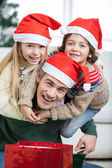 Playful Father Piggybacking Children During Christmas — Stockfoto
