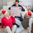 Man Holding Christmas Present While Parents Looking At Him — Stock Photo #34872175