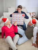 Man Holding Christmas Present While Parents Looking At Him — Stock Photo