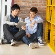 Male Students Using Digital Tablet While Sitting In Library — Stock Photo