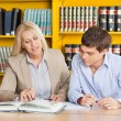 Teacher Explaining Student While Sitting At Table In Library — Stock Photo #34905673